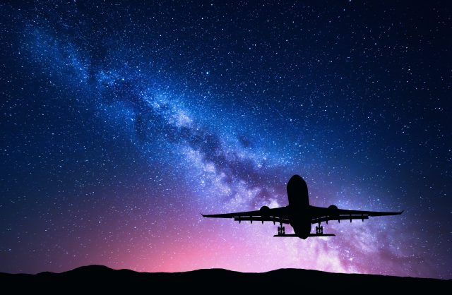 Milky Way and silhouette of a airplane. Landscape with passenger airplane is flying in the starry sky at night. Space background. Landing airliner on the background of colorful Milky Way. Aircraft